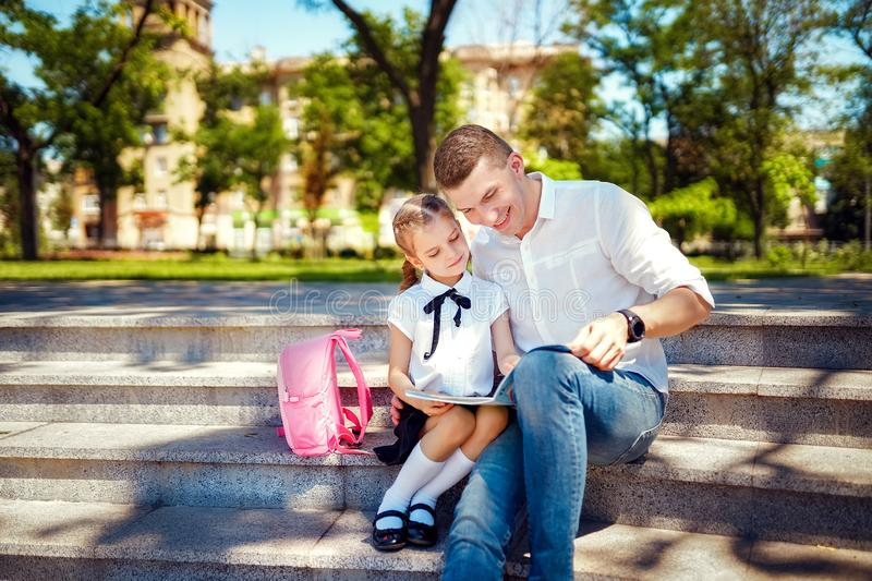 First day at school. Father and little kid daughter sitting on stairs and read book, study lessons. Parenthood and child stock image