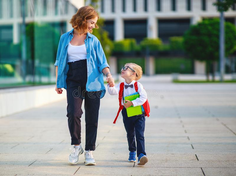 First day at school. mother leads  little child school boy in first grade stock images