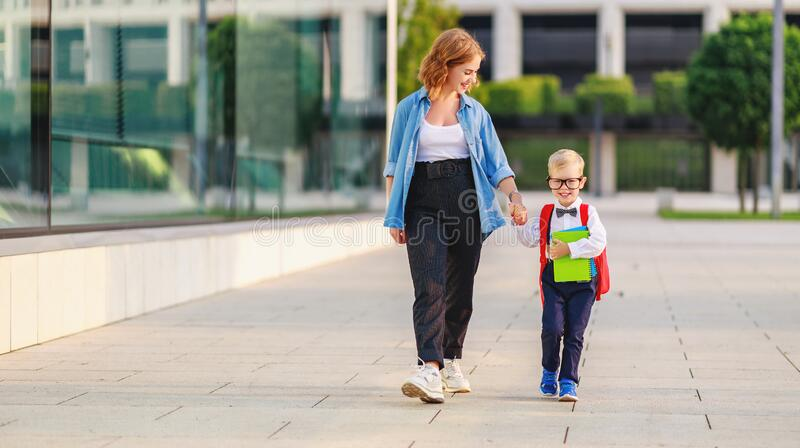First day at school. mother leads  little child boy in grade stock photos