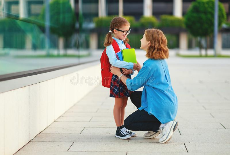 First day at school. mother leads  little child school girl in first grade royalty free stock photo