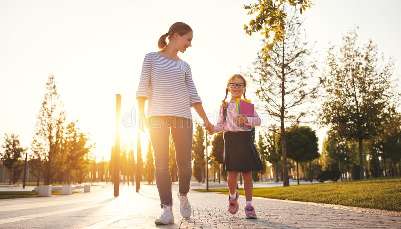 First day at school. mother leads little child school girl in f stock photos