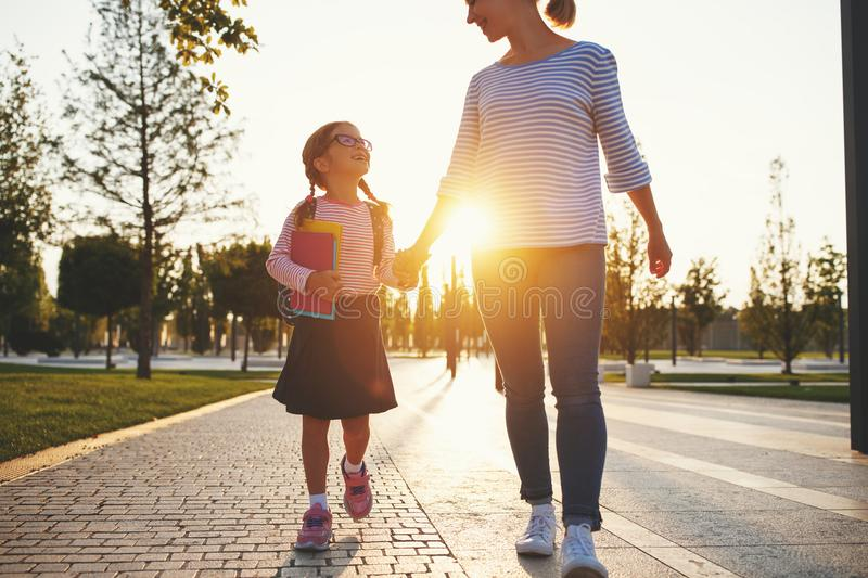 First day at school. mother leads little child school girl in f royalty free stock images