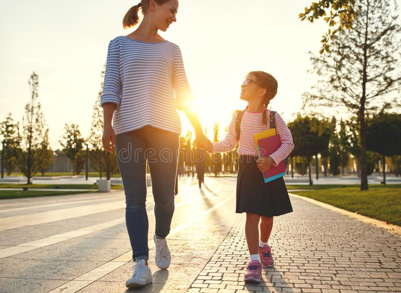First day at school. mother leads little child school girl in f royalty free stock photo