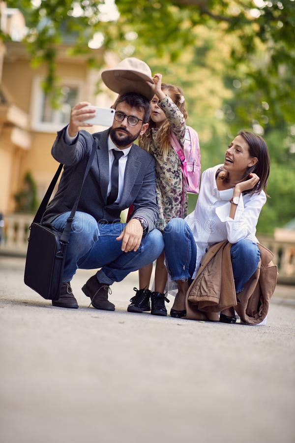 First day at school, parents and girl making a photo in front of school stock image