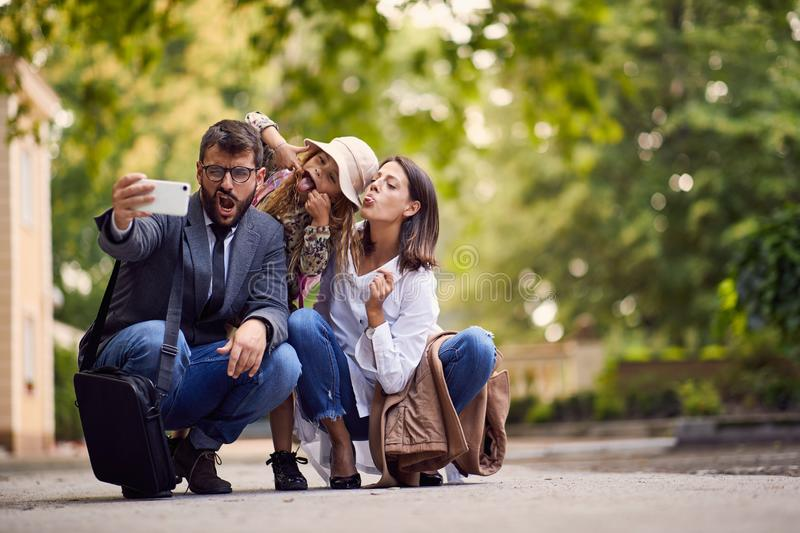 First day at school, parents and girl making a photo in front of school royalty free stock image