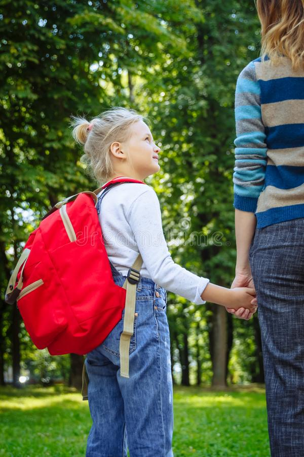 First day at school. Woman and girl with red backpack behind the back. Beginning of lessons. First day of fall. Back to royalty free stock image