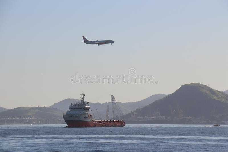 First day of summer in Brazil. Rio de Janeiro, Brazil, December 21, 2016: Airplane over flies ship in Guanabara Bay. Summer officially began in Brazil this royalty free stock images