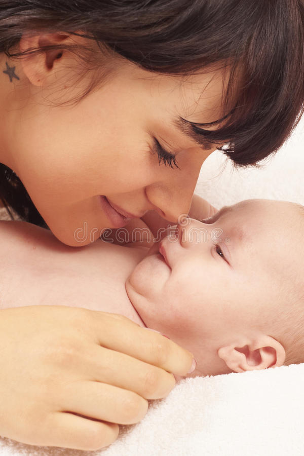 First days of meeting the own baby. Young and beautiful mother with her newborn baby. First meetings of both. Image taken as a closeup over white background stock photos