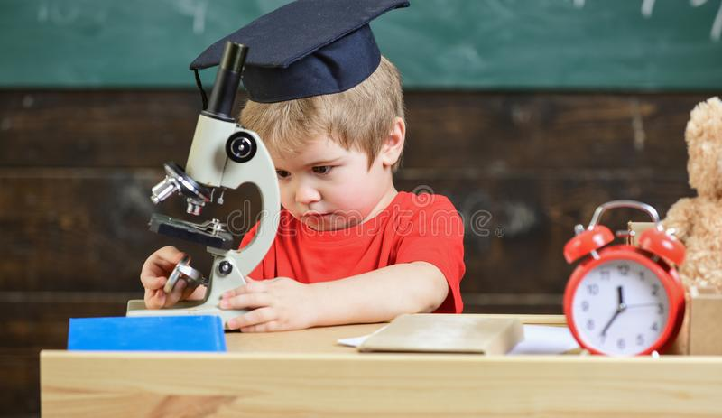 First former interested in studying, learning, education. Kid boy in academic cap work with microscope in classroom royalty free stock images