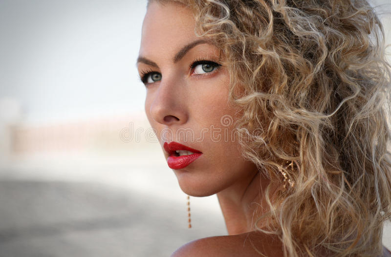 At first glance. Woman looking at you, woman ith curly hair and red lips stock photography