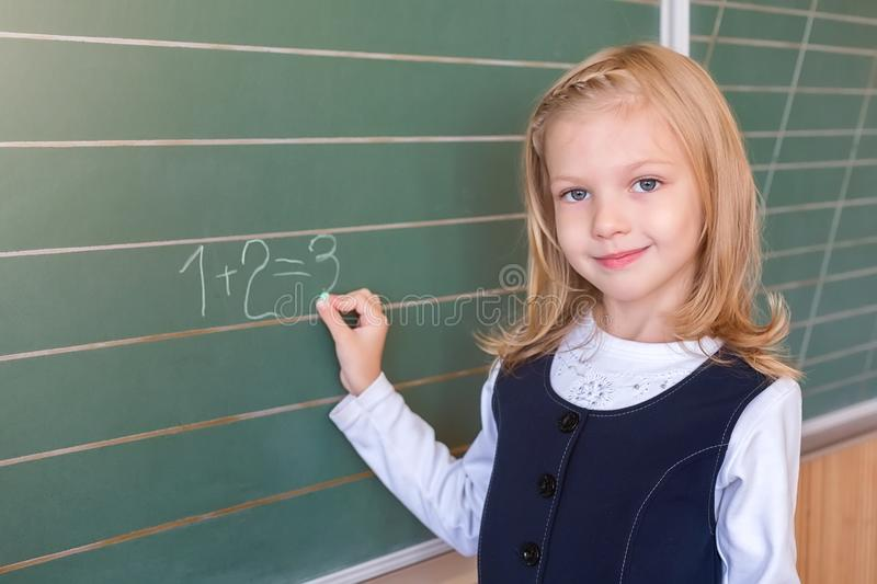 First grade pupil a girl writing on green blackboard at school lesson royalty free stock photography