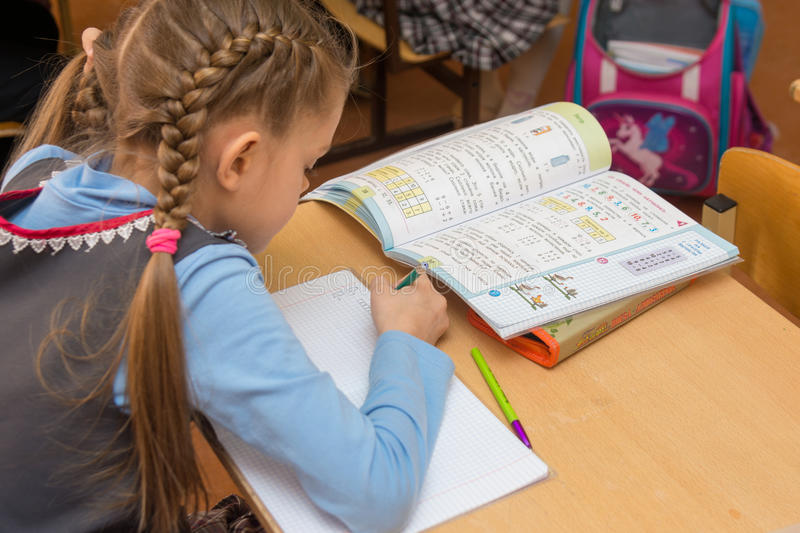 First-grader at a lesson of mathematics writes in a notebook, side view from the back stock photo