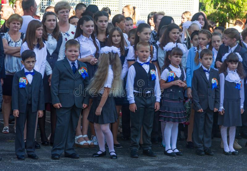 First-graders with high school students on the day of knowledge on September 1 in the schoolyard stock images