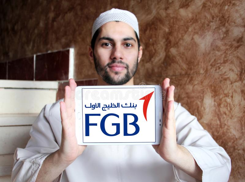 First Gulf Bank, FGB, logo. Logo of First Gulf Bank on samsung tablet holded by arab muslim man. First Gulf Bank is the third largest bank by assets in the stock image