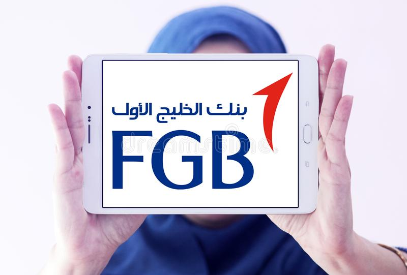 First Gulf Bank, FGB, logo. Logo of First Gulf Bank on samsung tablet holded by arab muslim woman. First Gulf Bank is the third largest bank by assets in the royalty free stock photos