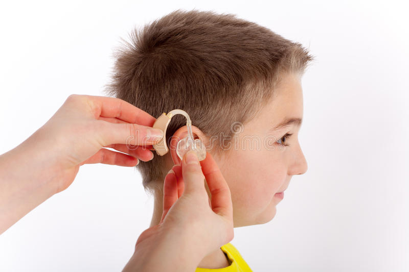 First hearing aid. Cute boy getting his first hearing aid stock images