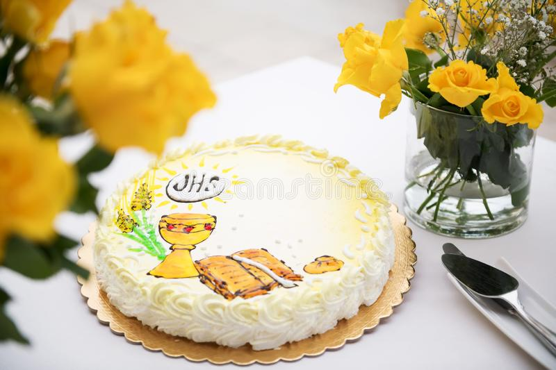 First holy communion concept, beautiful cake with first holy communion and yellow roses on a white table royalty free stock photo