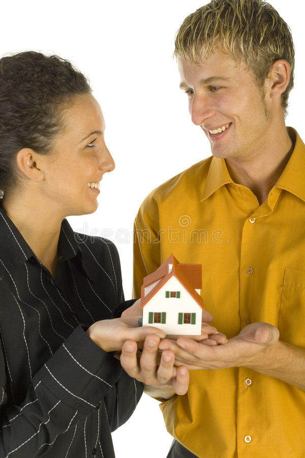 First house. Young, happy couple holding house miniature. They're looking at each other. White background stock photos