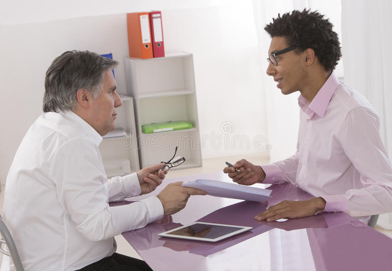 First job contract signature with young trainee. In manager office stock photography