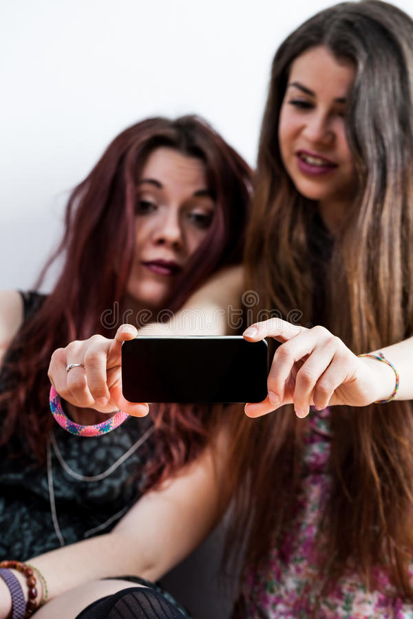 But first let's take a selfie. Young women taking a selfie or watching something on a smartphone royalty free stock images