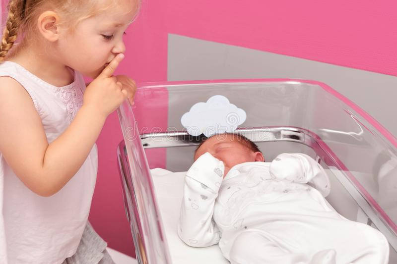 First meeting between a sister and a newborn baby in the hospital ward stock photos