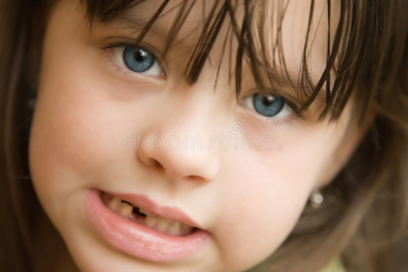First missing tooth. Little girl with big blue eyes showing her first missing tooth royalty free stock images