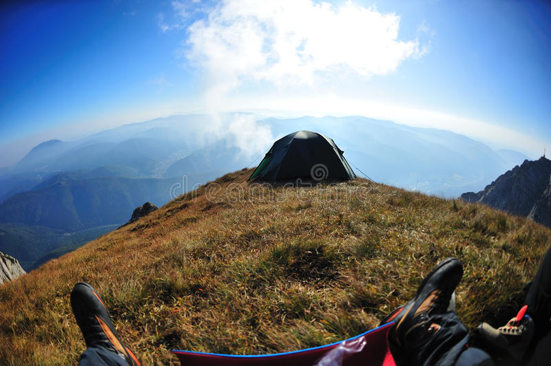 First person shot of tent on alpine cliff edge royalty free stock image
