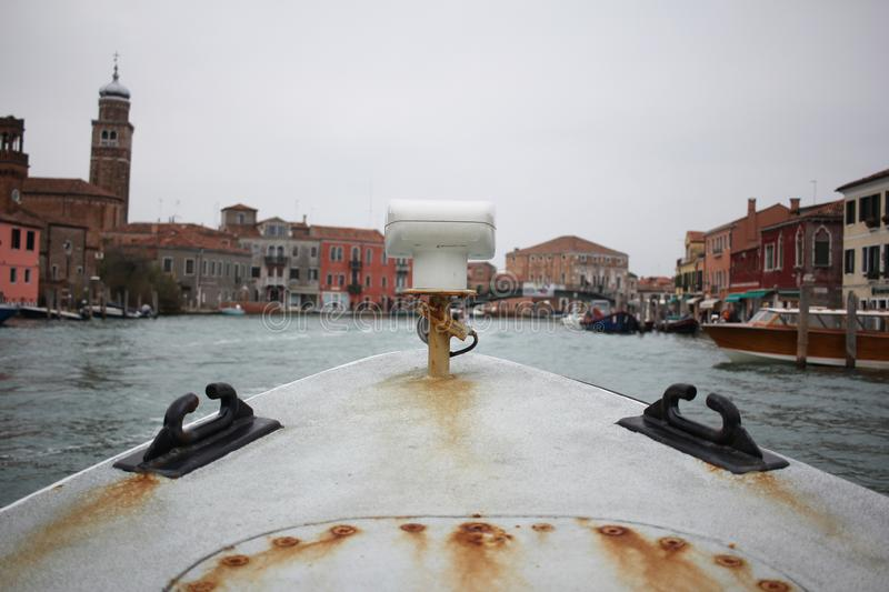 First person view of ancient rusty metal boat with old italian venice city and river scape cloudy Sky stock photos