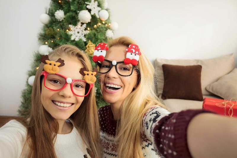 First person view of beautiful young mother and her teenage daughter taking a selfie in front of a decorated Christmas tree royalty free stock photo