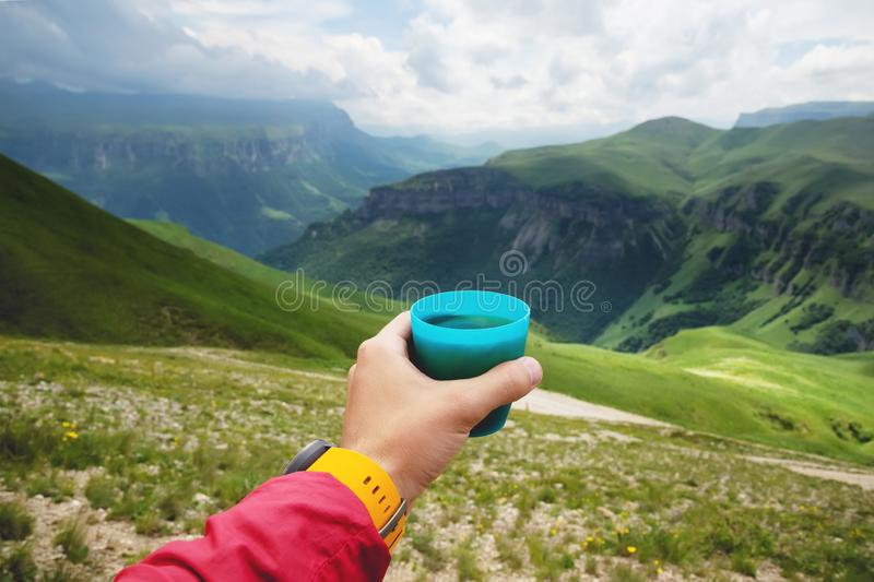 First-person view of a man`s hand holding a plastic cup of tea against a plateau of green hills and a cloudy sky in stock photo