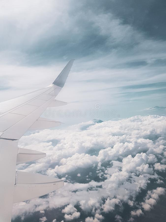 Airplane flying above the clouds. First person view of passenger looking on airplane`s wing flying above the clouds royalty free stock images