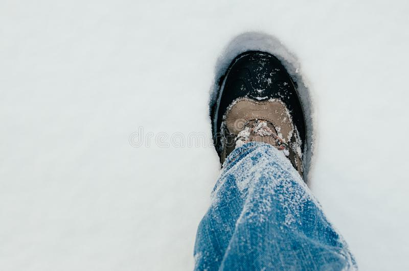 Hiking travel in winter on feet. First person view of right leg in blue jeans and dark brown boot, walking in the snow. Selective focus, close up image. Hiking royalty free stock image