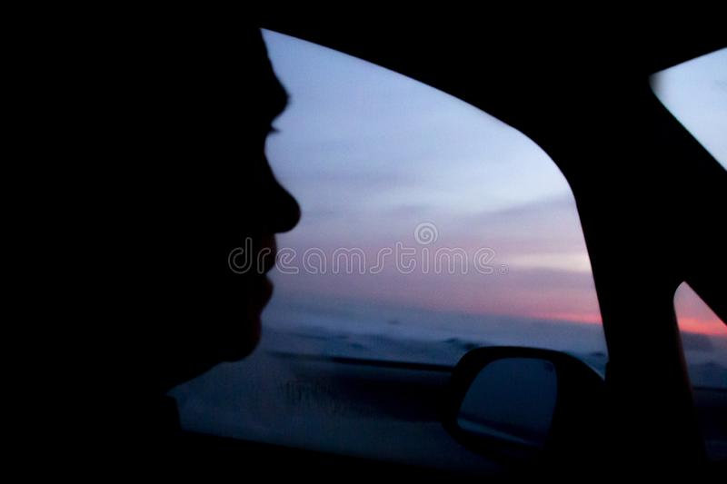 The first pink streak of dawn in the dark window of the car on the background of glowing sky. stock image