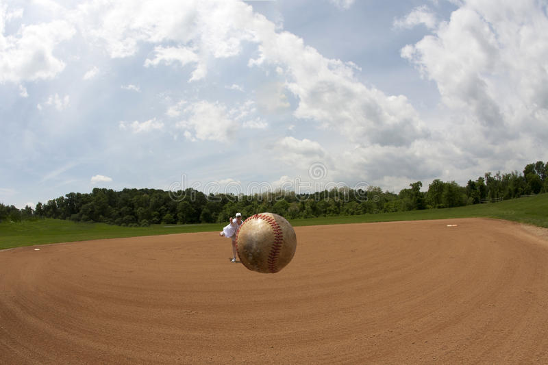 First Pitch. Fisheye view of a baseball apparently hovering in mid air with female softball pitcher in the background stock photo