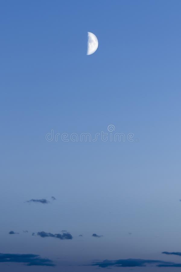 Half moon against the background of the night blue sky with dark clouds, abstract background stock photography