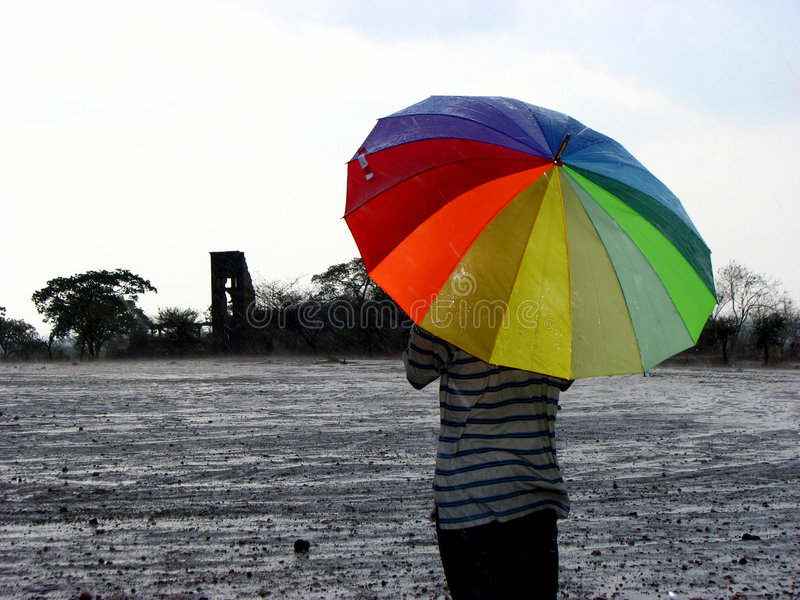 The First Rains. A guy standing in the first seasona rains with a colorful umbrella in front of a vast ground royalty free stock photo