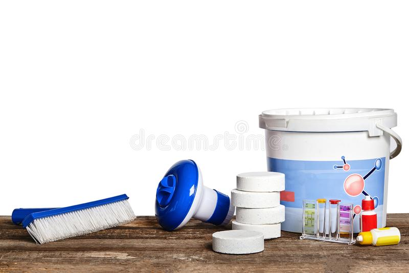Equipment with chemical cleaning products and tools for the maintenance of the swimming pool on a wooden surface against. First-rate equipment with chemical royalty free stock image