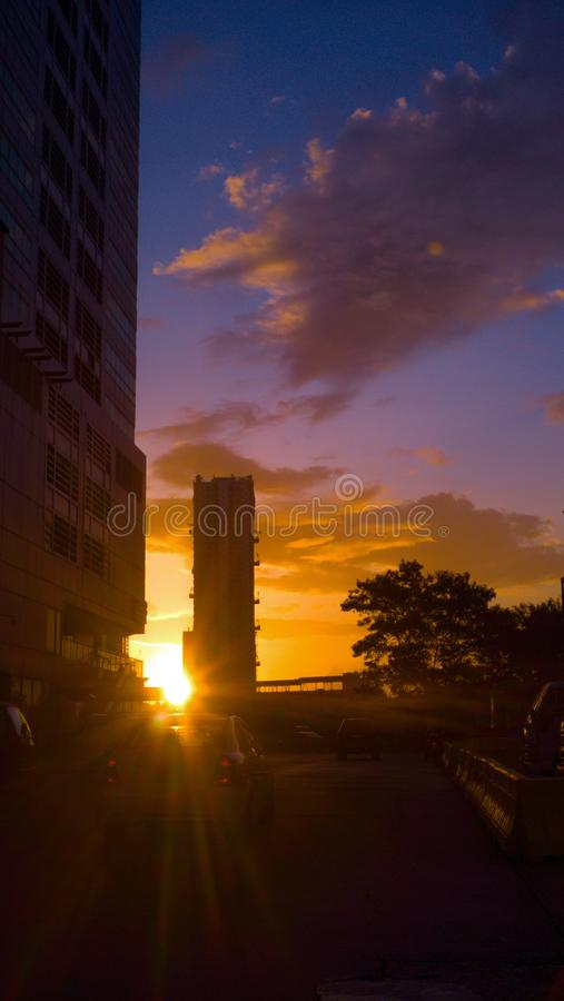 Sun rises upon the city. First rays of a rising sun peaks between buildings of this busy city and in the horizon orange colors of the coming day meet the deep stock photo