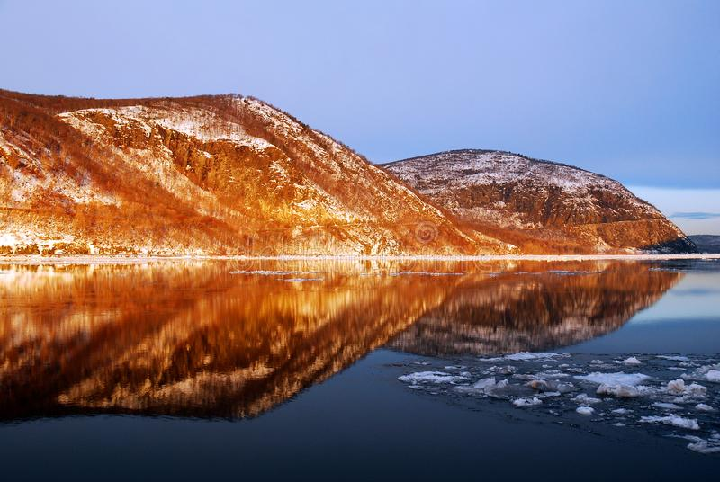 The first rrays of light on the Hudson Highlands in winter. The first rrays of light on the Hudson Highlands and an icy Hudson River in winter royalty free stock image