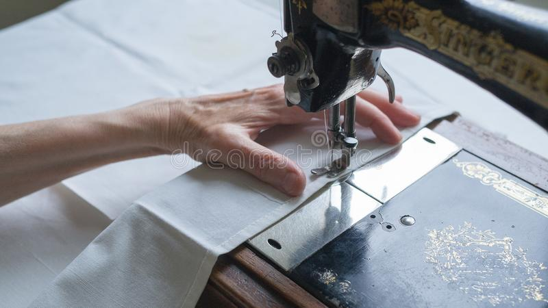 First SINGER sewing machine. Sewing process. Foot of old vintage sewing machine and hands of elderly woman. Selective stock images