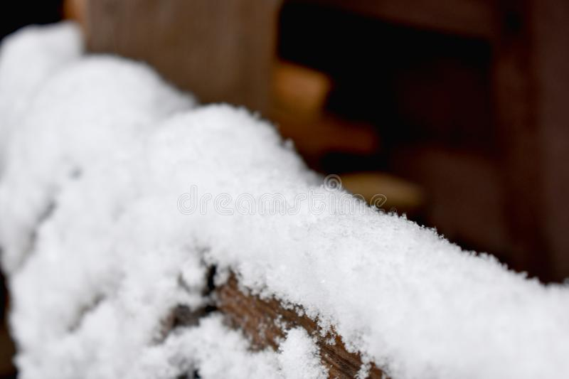 First snow on the wooden table. An image of the very first thin snowflakes laying down on a wooden construction table in a fenced yard stock images