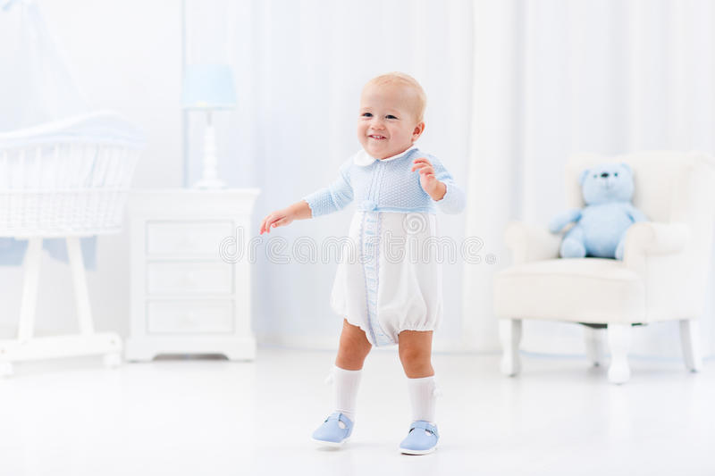 First steps of baby boy learning to walk stock images