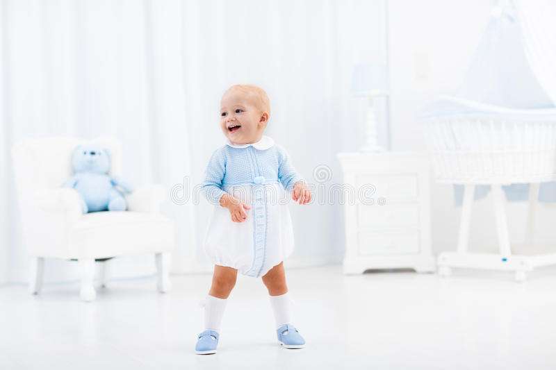 First steps of baby boy learning to walk stock photos