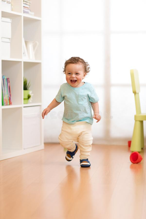 First steps of baby boy toddler learning to walk in living room. Footwear for little children. royalty free stock photos