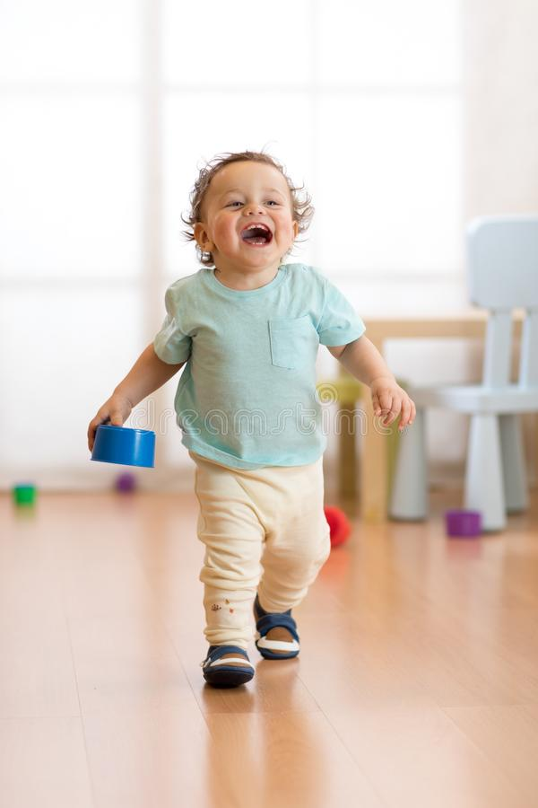 First steps of baby boy toddler learning to walk in living room. Footwear for little kids. stock photo