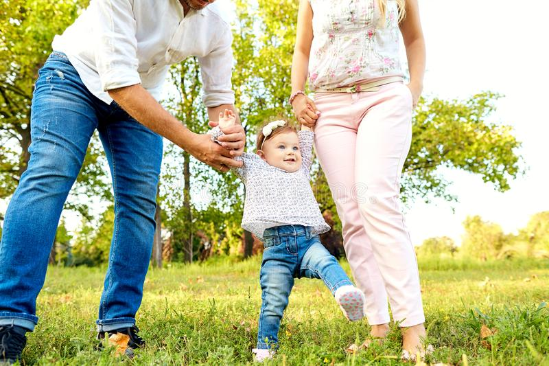 The first steps of the baby. Parents are teaching their child to stock photo