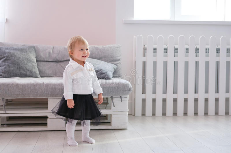 First steps of baby girl learning to walk in white sunny bedroom stock photos