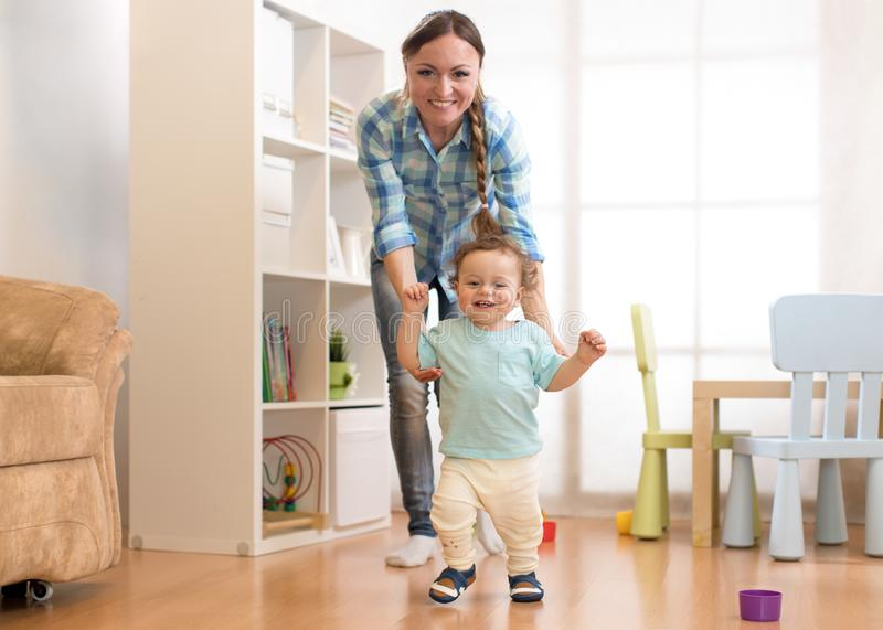 First steps of baby toddler boy learning to walk in white sunny living room. Footwear for child. royalty free stock images