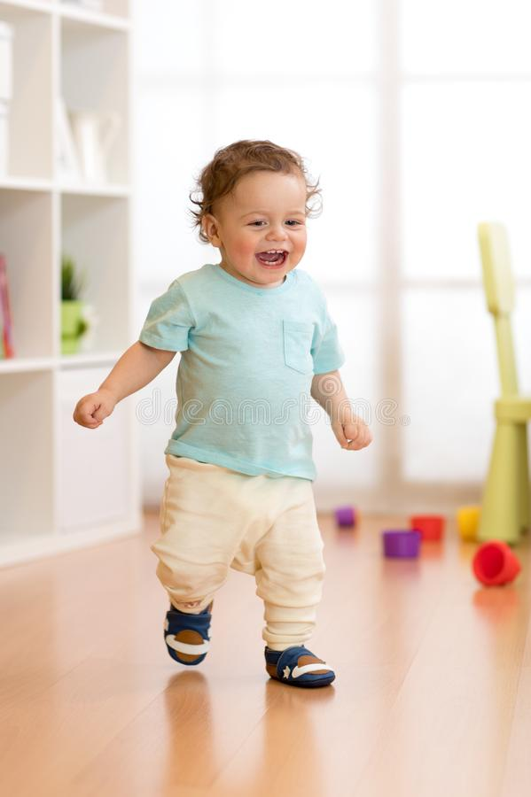 First steps of baby boy toddler learning to walk in living room. Footwear for little children. stock photography