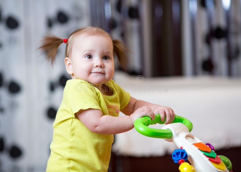 First steps of little child girl in baby walker royalty free stock photography